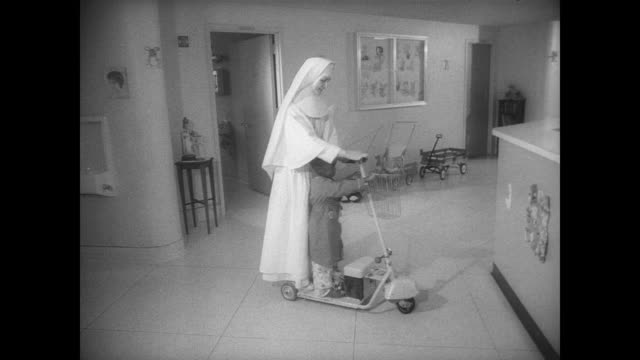 the nuns of st elizabeth's hospital save time in long hallways by riding electric scooters / nuns exchange notes as one stands on a scooter / nurse... - nun stock videos & royalty-free footage