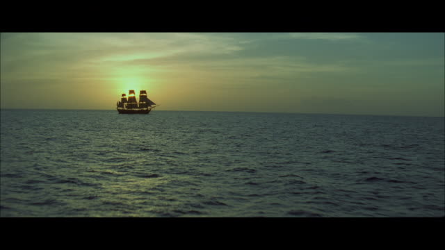 aerial the ocean at dawn, with a sailing ship becalmed against the sun - nave a vela video stock e b–roll