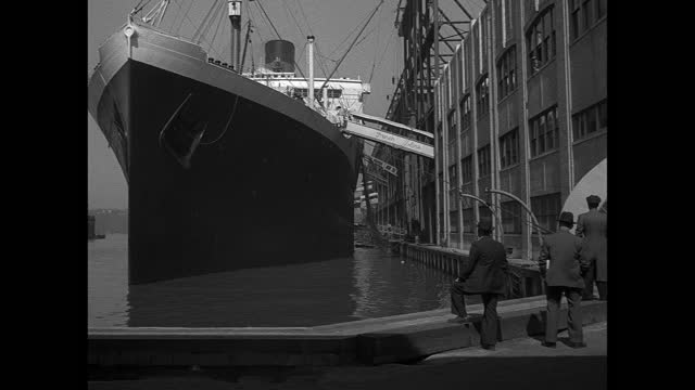 the ocean liner ile de france berthed next to a terminal building. - 1930 stock-videos und b-roll-filmmaterial