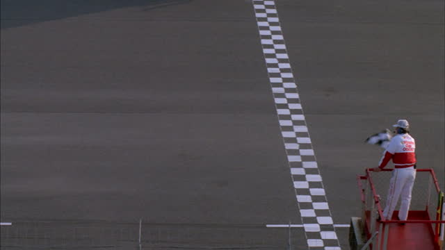 the official waves the checkered flag at the end of a nascar race. - finishing stock videos & royalty-free footage
