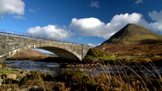 T/L 4K The old bridge of Sligachan with the rocky mountains of Cuillin on the background