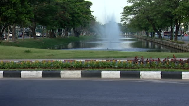 the old city moat, chiang mai. view of a busy road in the foreground with an elegantly landscaped canal lined with water fountains, in the background. - 堀点の映像素材/bロール