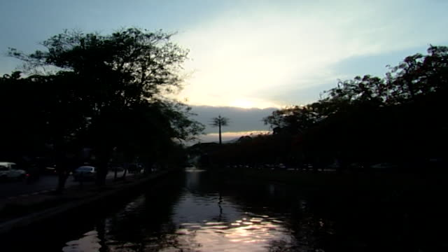 the old city moat, chiang mai. view of a cloud-covered sunset reflecting upon the waters of the moat. - moat stock videos & royalty-free footage