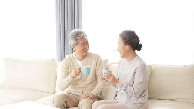 vidéos et rushes de the old couple holds the cup sitting on the couch with a smile - 60 64 ans