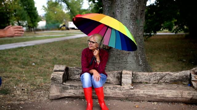vídeos de stock, filmes e b-roll de o old casal na chuva com guarda-sóis - chapéu