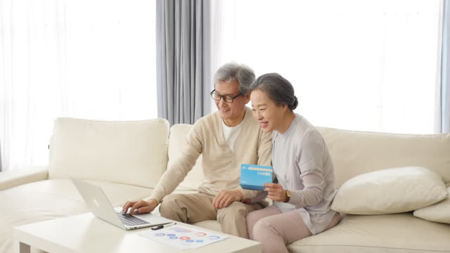 vidéos et rushes de the old couple looks at laptop holding a bankbook in the living room - seniornaute