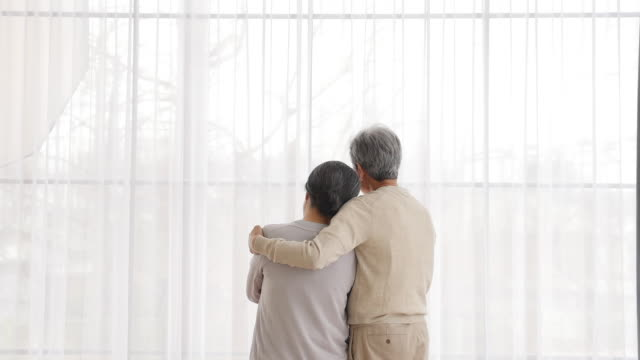vidéos et rushes de the old couple looks out the window in the living room - 60 64 ans