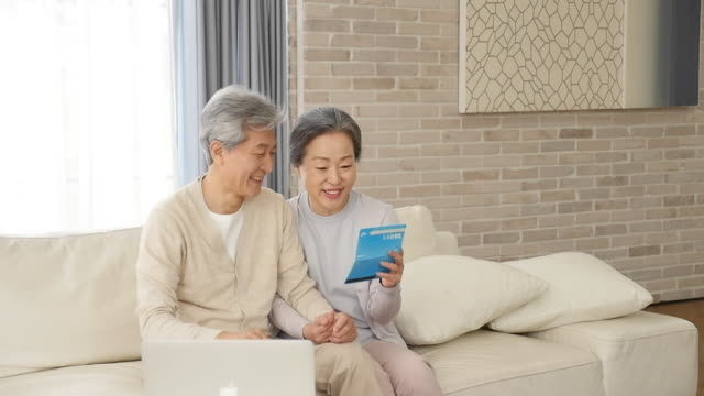 vidéos et rushes de the old couple talks and looks at the bankbook in the living room - seniornaute