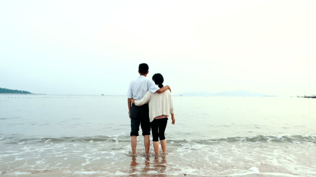 The old couple walking at sea beach
