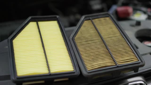 使用後の古いフィルタと車のブランドの新しい車のエアフィルター - 交代点の映像素材/bロール