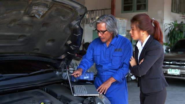 the old man mechanic and woman customer discussing repairs done to her vehicle. - automobile industry stock videos & royalty-free footage