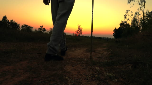 vídeos de stock e filmes b-roll de the old man using staff walking during sunset, concept healthy - bengala acessório