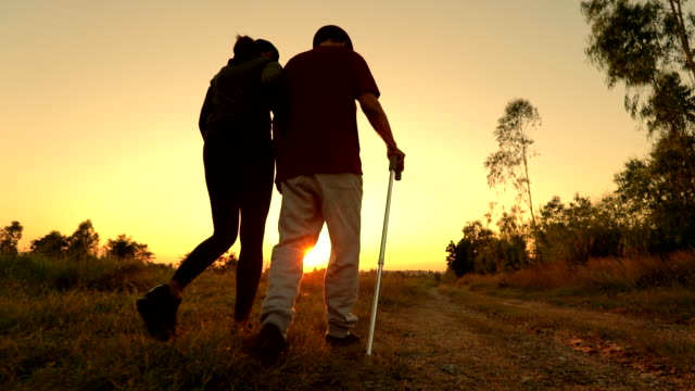 the old man using staff walking with his daughter during sunset, slow motion - alzheimer's disease stock videos & royalty-free footage