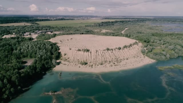 the old sand quarry has turned into a lake with clear water. - quarry stock videos & royalty-free footage