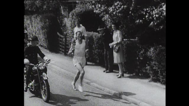 the olympic torch is carried by a relay of english runners on its way to the 1948 london olympic games. - flaming torch stock videos & royalty-free footage