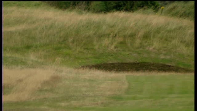 royal birkdale course fairway being mown / flag on hole / grass with stand in background / bunker / flag flying on hole - the open championship stock-videos und b-roll-filmmaterial