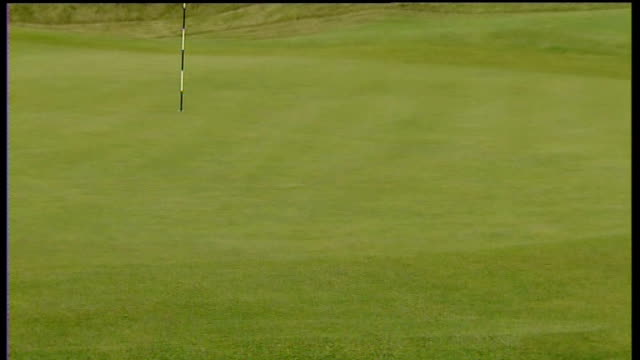 royal birkdale course rake in bunker / flag in hole on green / green / sand in bunker being beaten with machine / sand being raked / leaves being... - the open championship stock-videos und b-roll-filmmaterial