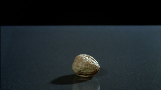The open palm of a Caucasian male hand smashes a walnut shell.