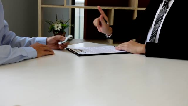 the operator employee submits documents and money to the manager while the manager denies the bribe. - bribing stock videos & royalty-free footage