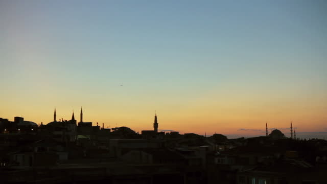 ws the orange glow over a city at dusk - formato panoramico con bande nere video stock e b–roll