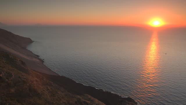 the orange sun sets over the tyrrhenian sea as seen from stromboli, italy. - mar mediterraneo video stock e b–roll