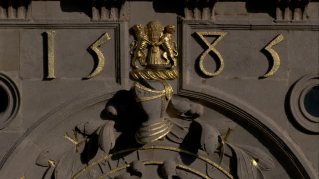 the ornate clock at burghley house displays the year 1585 and a coat of arms. available in hd. - リンカンシャー点の映像素材/bロール