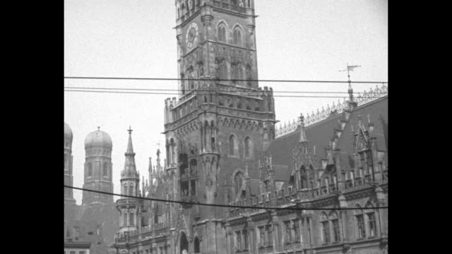 the ornate, gothic-style new town hall / on a two-level platform of the glockenspiel, figurines spin and a 'musical band' rolls left - rathaus stock videos & royalty-free footage