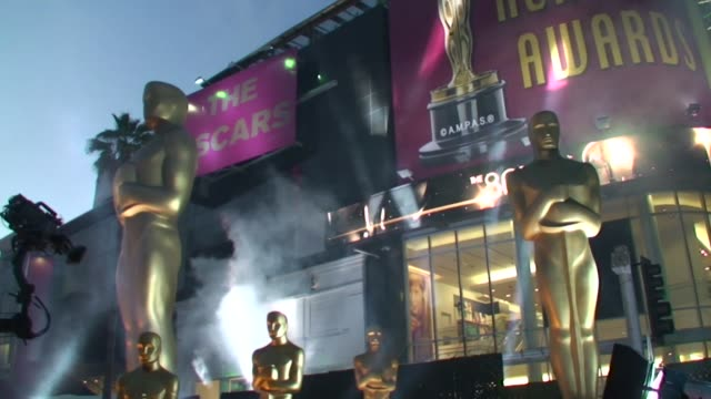 The Oscar Academy Awards establishing shot in all its glory outside on the Hollywood Highland complex with many large golden Oscar Statues lit with...