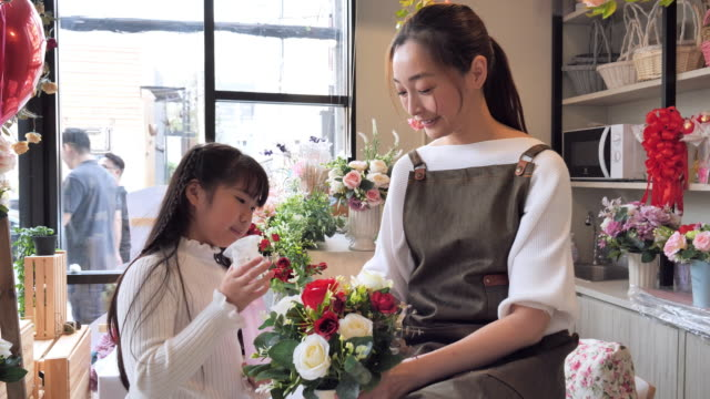 the owner of a asian flower shop with his daughter helps arrange the flowers inside the shop to prepare for the sale, a japanese woman with professional florists, small business concept. - fioraio negozio video stock e b–roll