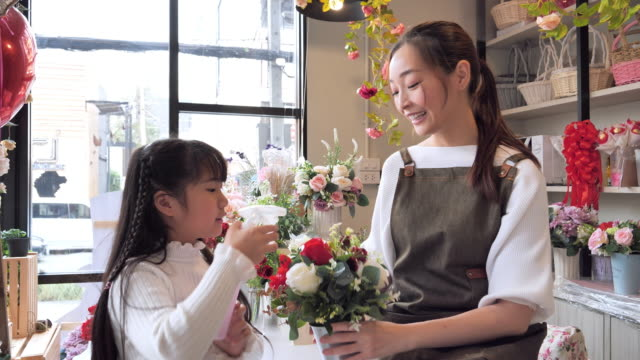the owner of a asian flower shop with his daughter helps arrange the flowers inside the shop to prepare for the sale, a japanese woman with professional florists, small business concept. - retail occupation stock videos & royalty-free footage