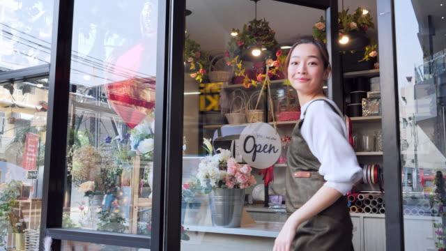 アジア女性フラワーショップのオープンショップのオーナーは、花を買いに来るお客様、プロの花屋、都会の花屋、中小企業のコンセプトを持つ日本人女性を歓迎します。 - フローリスト点の映像素材/bロール