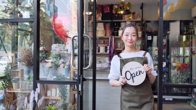the owner of the asian women's flower shop open shop welcomes customers who come to buy flowers, a japanese woman with professional florists, urban flower shops, small business concepts, - flower shop stock videos & royalty-free footage