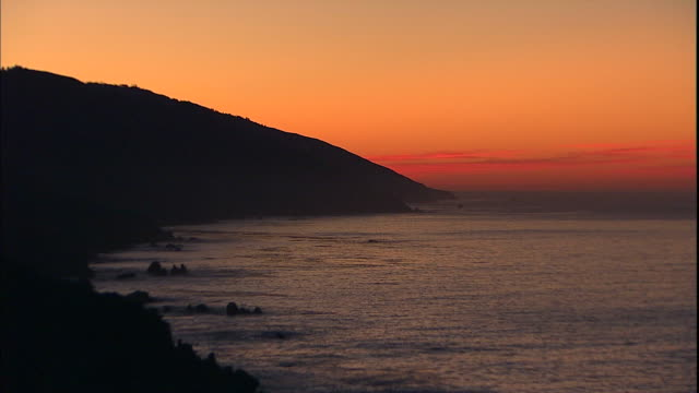 The Pacific Ocean glistens beneath a glowing orange sky.