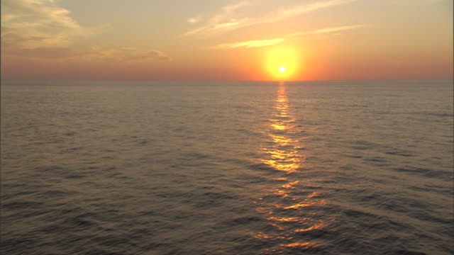 the pacific ocean reflects the setting sun. - sunset stock videos & royalty-free footage