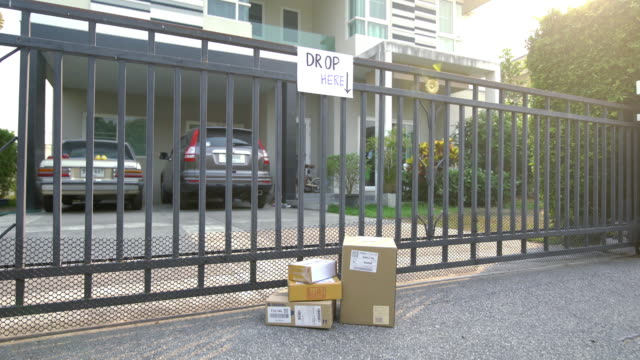 the package on the floor at front gate sent by delivery man in coronavirus covid-19 situation - gate stock videos & royalty-free footage