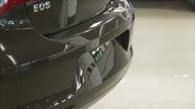 the paint of a volkswagen eos reflects images in a showroom. - automobilindustrie stock-videos und b-roll-filmmaterial