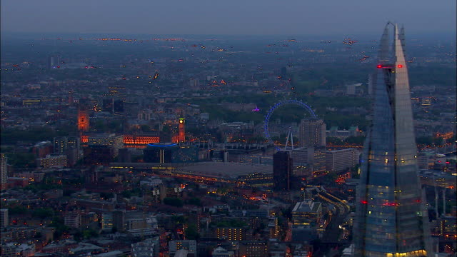 vídeos y material grabado en eventos de stock de the palace of westminster and the london eye glow beyond the shard in london, england at night. - torre victoria