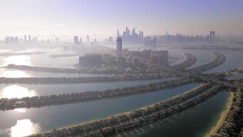the palm island in dubai united arab emirates aerial view at sunrise. famous artificial island with luxury villas and hotels - island stock videos & royalty-free footage
