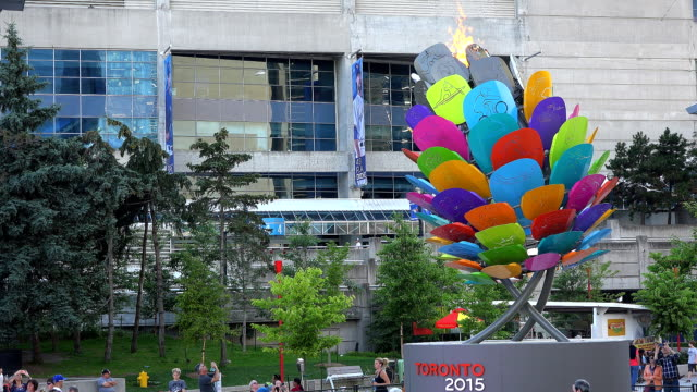 the pan am games of toronto 2015 flame burns brightly by the cn tower and the rogers centre / the cauldron has the shape of an acorn with the colors... - パンアメリカンハイウェイ点の映像素材/bロール