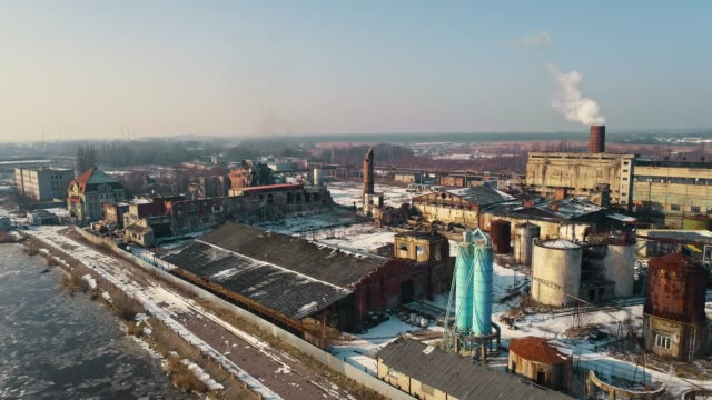 The panoramic view on the industrial district around the north port on the river covered by ice, with dock's cranes and commercial ships