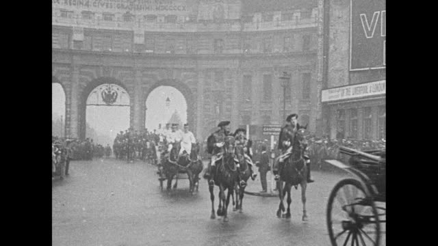 the parade with horse carriages trotting through the admiralty arch / elevated view of a conductor with his band on horseback with hundreds of people... - 1910 1919 video stock e b–roll