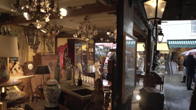 vidéos et rushes de the paris flea market in the pouring rain during winter. - antiquités