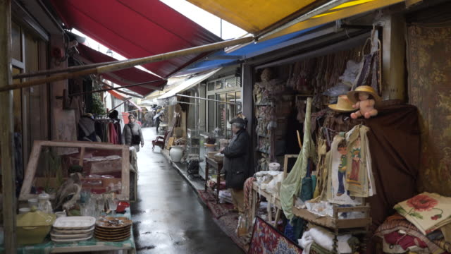 the paris flea market in the pouring rain during winter. - flea market stock videos and b-roll footage