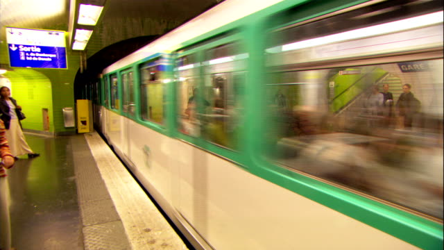 the paris metro speeds through the terminal and past passengers waiting on the platform. - underground rail stock videos & royalty-free footage
