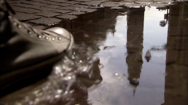 The Parma Cathedral bell tower reflects in a puddle of water. Available in HD.