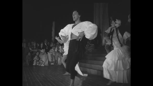 the party's host, fashion designer jacques fath, wears costume as he leads dancing group down steps and off stage as part of his carnival in rio... - haarzopf stock-videos und b-roll-filmmaterial
