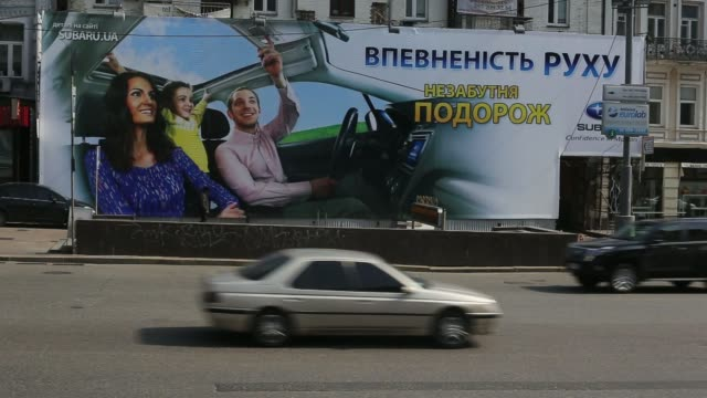 The Parus business center skyscraper stands on the skyline in Kiev Ukraine on Saturday March 22 Road traffic passes a billboard advertisement for...