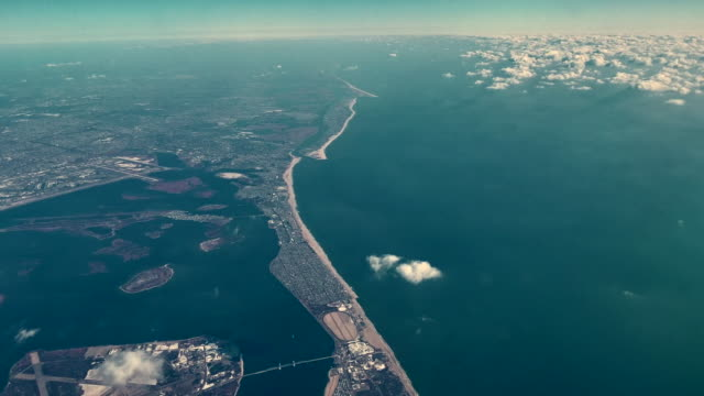 the passenger aircraft flying over the ocean next to long island, new york, usa - long island stock videos & royalty-free footage