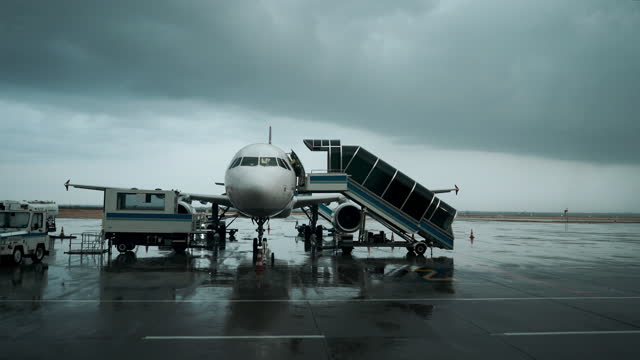 the passenger aircraft waiting on airport apron on rainy weather - aircraft carrier stock videos & royalty-free footage