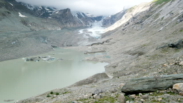 the pasterze glacier is seen behind a lake in a basin the glacier once filled with ice that in 1963 was still approximately 100 meters deep on august... - human tongue stock videos & royalty-free footage